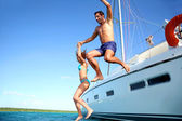 Young couple jumping in water from yacht — Stock Photo