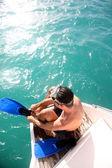Jonge man op een boot stappen flippers zetten — Stockfoto