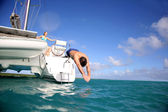 Man diving from catamaran deck into the sea — Stock Photo