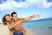 Man giving piggyback ride to girlfriend at the beach — Stock Photo