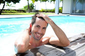 Portrait of smiling guy in swimming pool — Stok fotoğraf