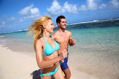 Couple running on sandy beach in caribbean island — Stock Photo