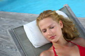 Blond woman in red bikini relaxing by pool — Stock Photo