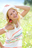 Smiling girl in countryside wearing hat — Stock Photo