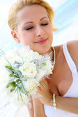 Portrait of beautiful bride standing by the beach — Stock Photo