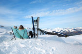 Couple of skiers relaxing in long chairs — Stock Photo