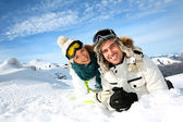 Couple of skiers laying down in the snow — Stock Photo