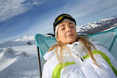 Woman in ski outfit relaxing in long chair — Stock Photo