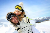 Skier at the mountain giving piggyback ride to girlfriend — 图库照片