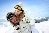 在山背驮式送女朋友的滑雪者 — 图库照片