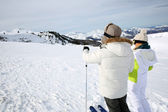 Back view of skiers looking at mountain scenery — Stock Photo