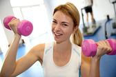 Happy woman in gym lifting dumbbells — Stock Photo