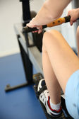 Woman using rowing equipment in gym center — Stock Photo