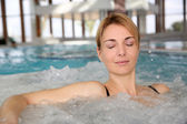 Portrait of woman relaxing in jacuzzi — Stock Photo