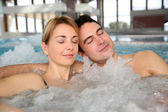 Couple relaxing in jacuzzi of spa center — Stock Photo