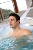 Man relaxing in massage pool — Stock Photo