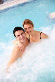 Couple enjoying jacuzzi in spa center — Stock Photo
