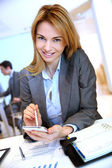 Businesswoman writing on pda digital screen — Stock Photo