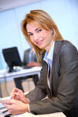 Businesswoman in office sitting at desk — Stockfoto