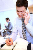 Businessman on the phone writing notes on agenda — Stock Photo