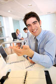 Cheerful salesman working on laptop computer — Stock Photo
