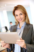 Businesswoman standing in office with tablet — Stock Photo