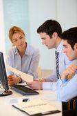 Business team working in front of desktop — Stock Photo