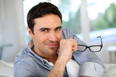 Good-looking man with eyeglasses sitting on sofa — Stock Photo