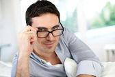 Good-looking man with eyeglasses sitting on sofa — Stock Photo