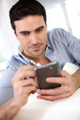 Modern guy using martphone at home — Stock Photo