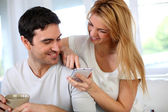 Cheerful woman showing smartphone to boyfriend — Stock Photo