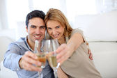 Cheerful couple celebrating with glass of sparkling wine — Stock Photo
