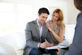 Couple signing terms of real-estate contract — Stock Photo