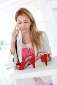 Woman in shoe store talking on the phone — Stockfoto