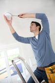 Electrician installing fire alarm inside house — Stock Photo