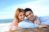 Happy couple leaning on a fence by the sea — Stock Photo