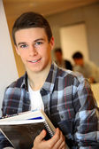 Student boy in class holding books — Stock Photo