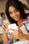 Student girl using smartphone in class — Stock Photo