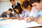 Group of teenagers in class writing an exam — Stock Photo