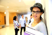 Trendy teen girl standing in school building — Stock Photo