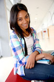 Cheerful student girl sitting on school bench — Stock Photo