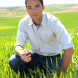 Farmer kneeling in wheat field — Stock Photo