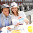 Cheerful couple looking at traveler guide in Madrid — Stock Photo