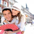 Man giving piggyback ride to girlfriend in Madrid — Stock Photo