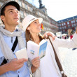 Tourists walking in LPlazMayor with traveler guide — Stockfoto #27930223