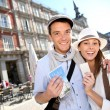 Cheerful couple showing visitor pass of Madrid — Stock Photo