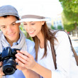 Cheerful couple with photo camera in touristic area — Stock Photo