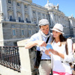 Couple reading traveler book by the Royal Palace of Madrid — Stock Photo #27930367