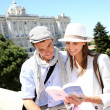 Couple reading traveler book by the Royal Palace of Madrid — Stock Photo #27930371