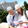 Couple reading traveler book by the Royal Palace of Madrid — Stock Photo #27930377